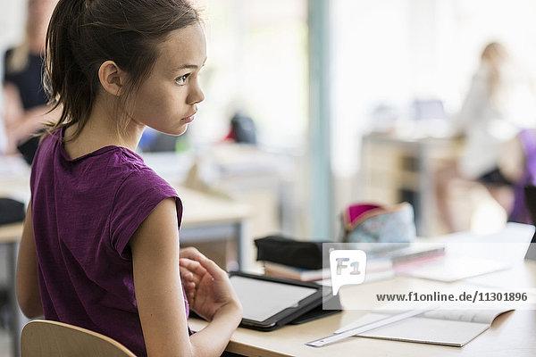 Rückansicht des Mädchens auf dem Stuhl am Schreibtisch im Klassenzimmer