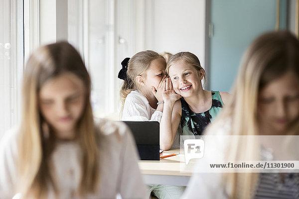 Glückliche Mädchen flüstern im Klassenzimmer
