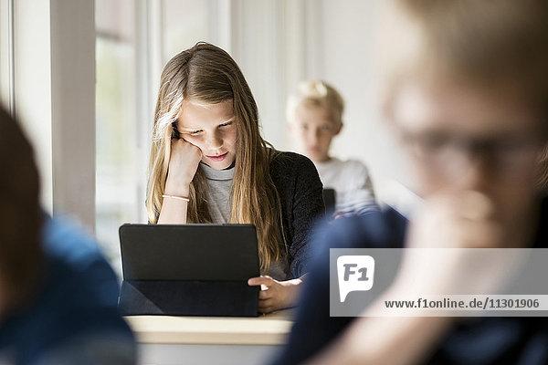 Mädchen lesen vom digitalen Tablett zum Lernen im Klassenzimmer