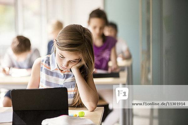 Schülerin am Schreibtisch mit Schülern im Klassenzimmer