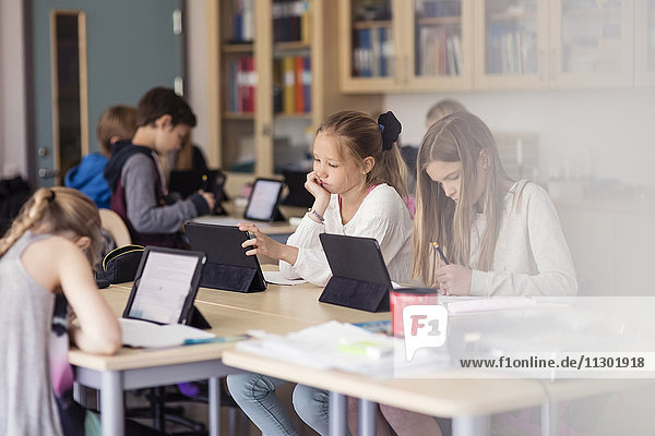 High-School-Kinder mit digitalem Tablett im Klassenzimmer