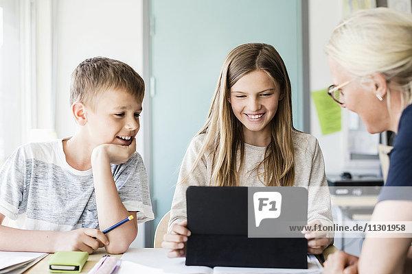 Fröhliches Mädchen mit digitalem Tablett  während Lehrer und Junge in der Schule im Klassenzimmer zuschauen.