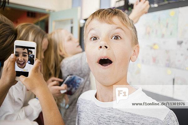 Überraschter Junge steht inmitten von Freunden  die Selfie auf dem Flur nehmen.