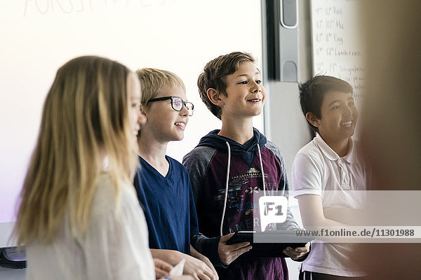 Zufriedene Schüler bei der Präsentation mit dem digitalen Tablett im Klassenzimmer