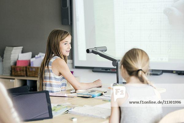Schulmädchen sitzen am Schreibtisch im Klassenzimmer