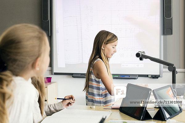 Seitenansicht des Lesedokuments des Mädchens unter der Kamera gegen das Whiteboard im Klassenzimmer