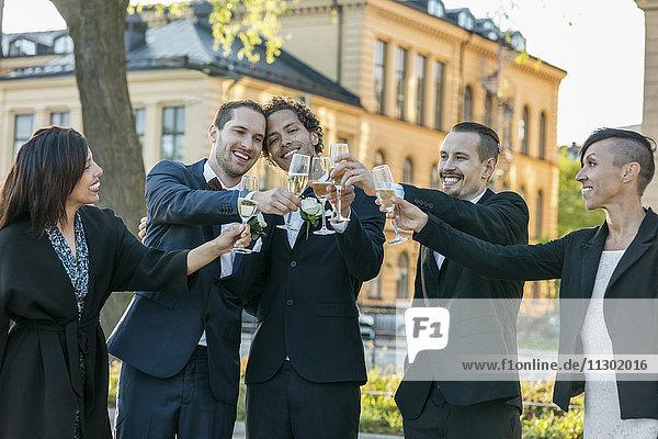 Glückliche Freunde  die Champagnerflöten für den Toast während der Hochzeitszeremonie zubereiten.