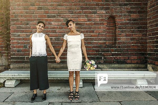 Glückliches jungvermähltes lesbisches Paar steht an der Ziegelmauer
