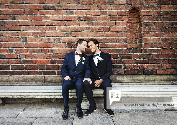 Newlywed gay couple sitting on bench against brick wall