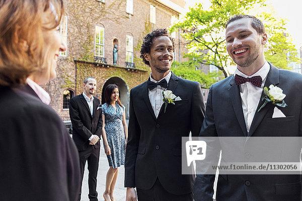 Fröhliches schwules Paar vor dem Priester mit Gast im Hintergrund bei der Hochzeitszeremonie