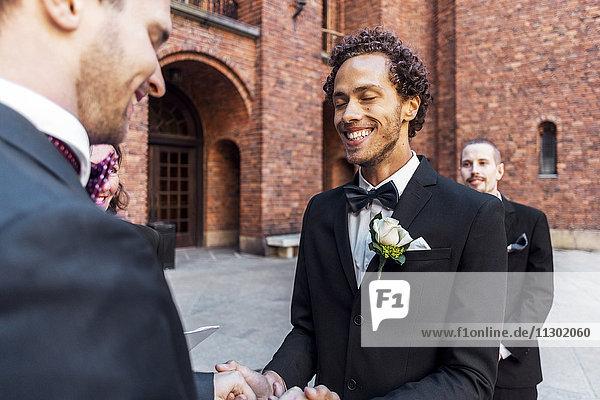 Mann hält Hände von schwulem Partner mit Freund im Hintergrund