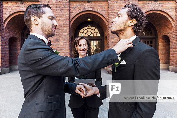 Mann  der die Fliege des schwulen Partners vor dem Priester während der Hochzeitszeremonie anpasst.