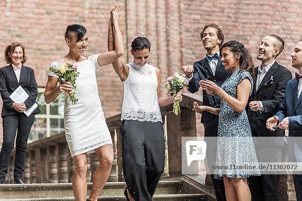 Flachwinkelansicht des fröhlichen lesbischen Paares auf der Treppe mit erhobenen Händen von Freunden