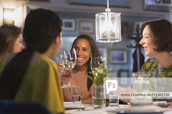 Lächelnde Freundinnen trinken Weißweingläser am Restauranttisch