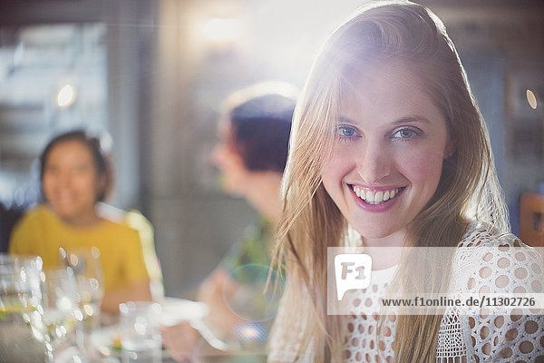 Portrait smiling woman dining with friends in restaurant