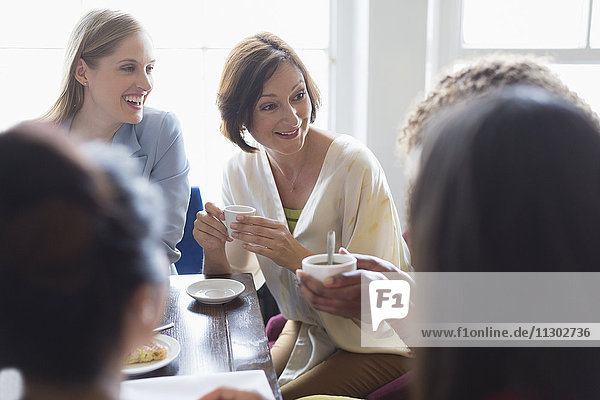 Women friends drinking coffee and talking at restaurant table