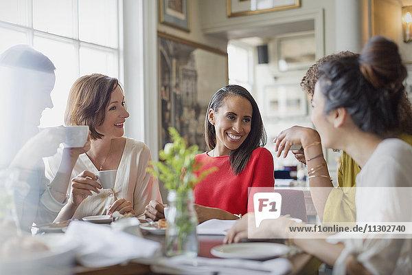 Lächelnde Freundinnen beim Kaffeetrinken am Restauranttisch