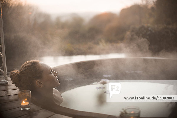 Serene woman soaking in steaming hot tub with autumn tree view