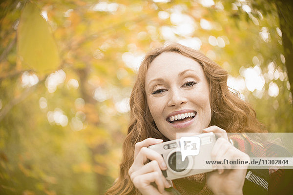 Portrait enthusiastic woman with digital camera under autumn trees