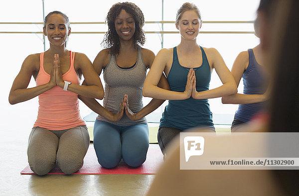 Lächelnde Frauen praktizieren Yoga mit den Händen im Herzzentrum im Fitnessstudio