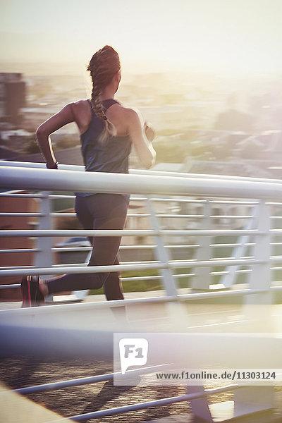 Female runner running on sunny urban footbridge at sunrise