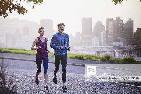 Runner couple running on urban city street