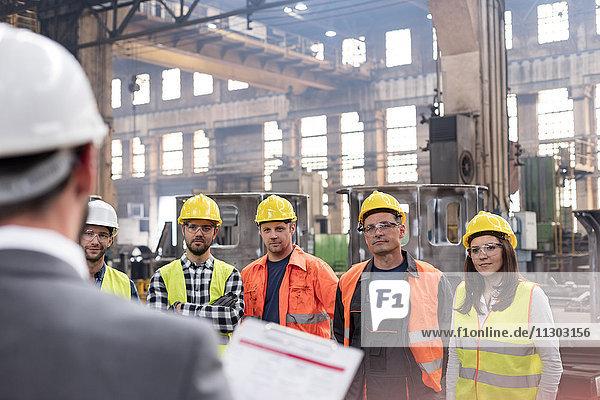 Stahlarbeiter hören dem Manager beim Treffen in der Fabrik zu