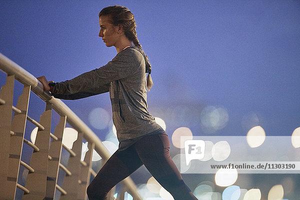 Determined female runner stretching legs on footbridge at dawn