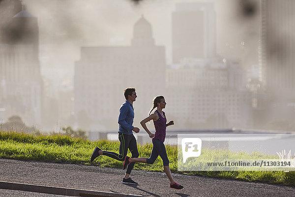 Runner couple running on sunny urban city sidewalk
