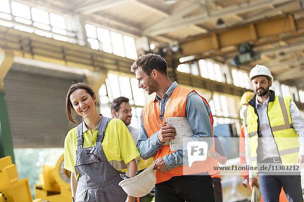 Stahlarbeiter beim Gehen und Reden in der Fabrik
