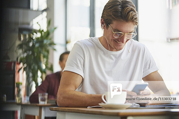 Smiling man with headphones using cell phone and drinking coffee in cafe