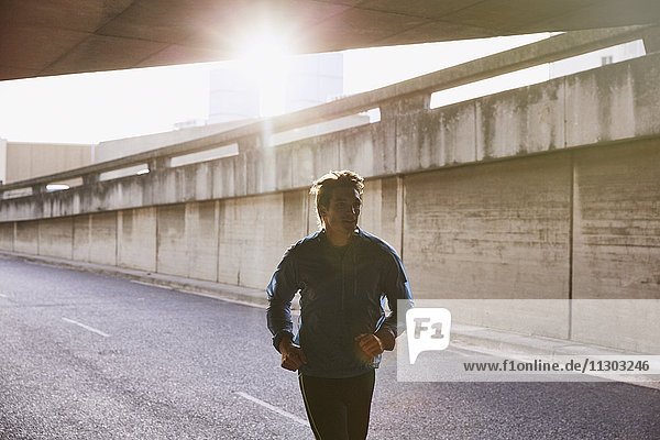 Male runner running into urban tunnel