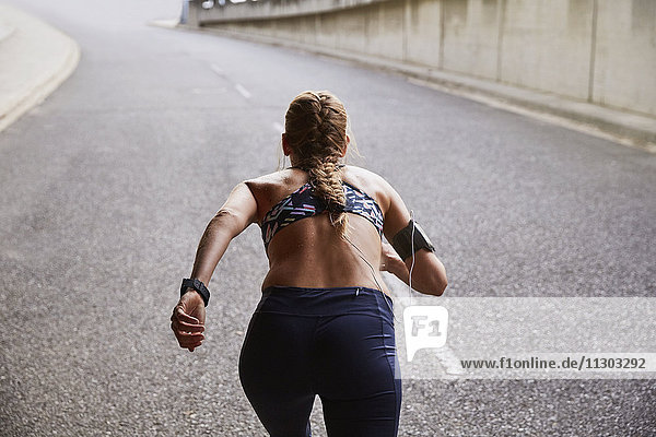 Fit female runner with mp3 player armband running on urban street