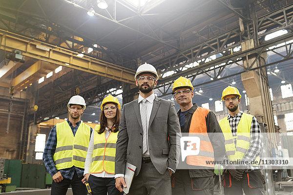 Porträt eines selbstbewussten Managers und Stahlarbeiter-Teams in der Fabrik