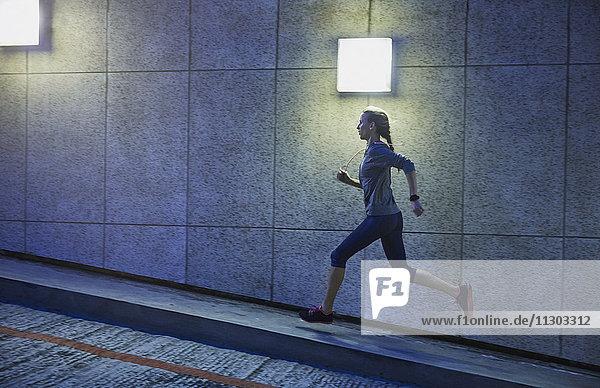 Female runner running ascending illuminated urban ramp
