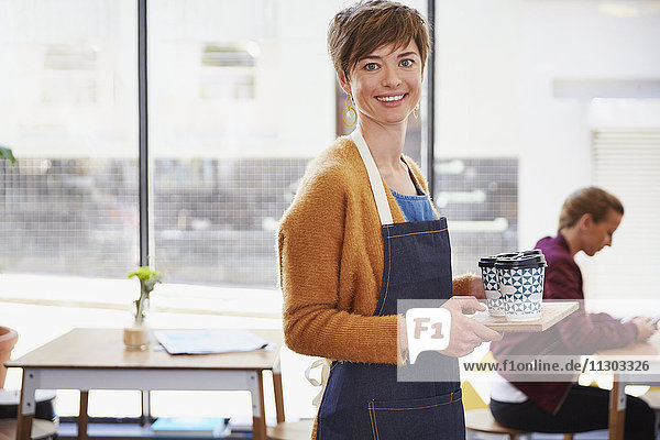 Portrait confident female cafe owner serving coffee on tray in cafe