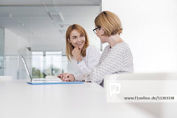 Geschäftsfrauen bei der Arbeit am Laptop im Konferenzraum