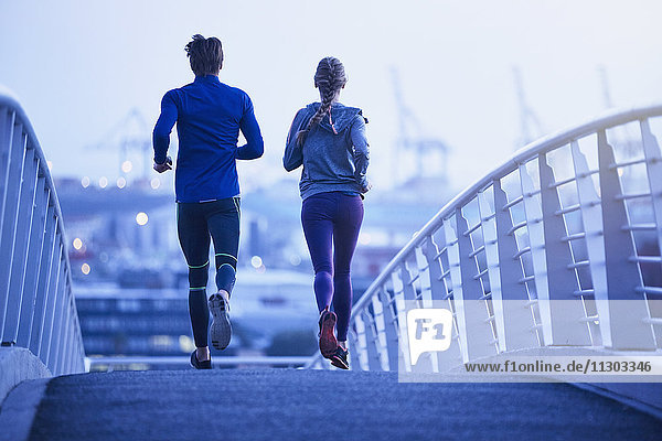 Runner couple running on urban footbridge at dawn