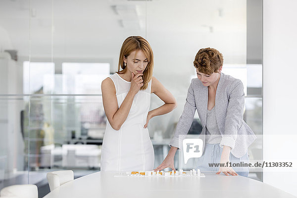 Architektinnen untersuchen Modell im Konferenzraum