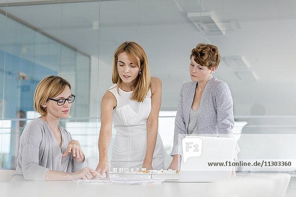 Architektinnen diskutieren Blaupause am Laptop im Konferenzsaal