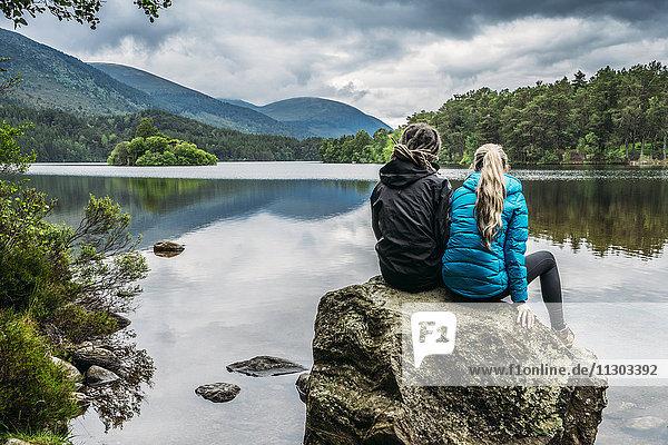 Paar auf Felsen sitzend mit Blick auf den ruhigen See  Loch an Eilein  Schottland