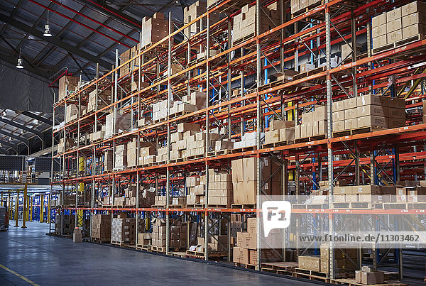 Cardboard boxes stacked on shelves in distribution warehouse