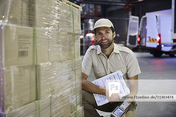 Portrait confident truck driver worker with scanner at pallet of cardboard boxes at distribution warehouse loading dock