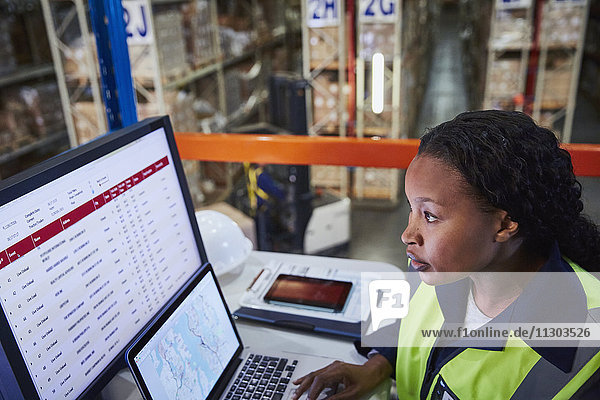 Focused female manager using laptop and computer in distribution warehouse