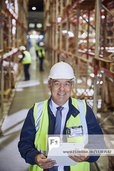Portrait smiling manager with clipboard in distribution warehouse