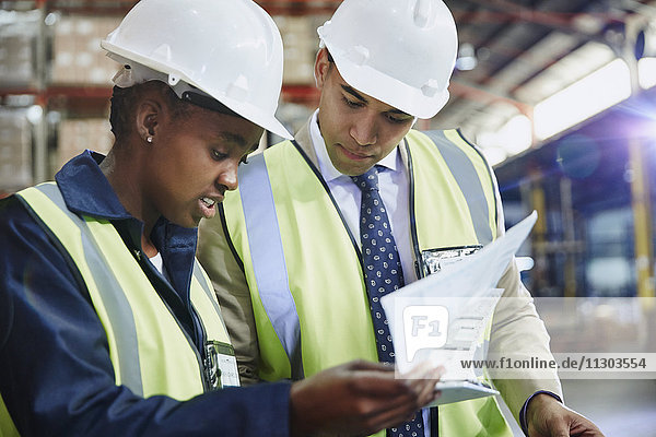 Manager and worker reviewing paperwork in distribution warehouse
