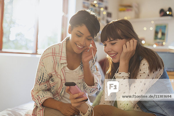 Young women friends sharing headphones listening to music with mp3 player