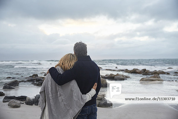 Serene affectionate couple hugging on winter beach looking at ocean