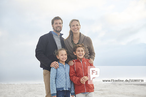 Portrait smiling family on winter beach
