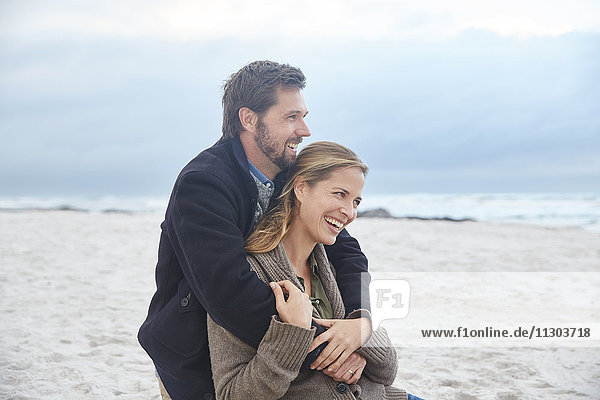 Happy couple hugging on winter beach